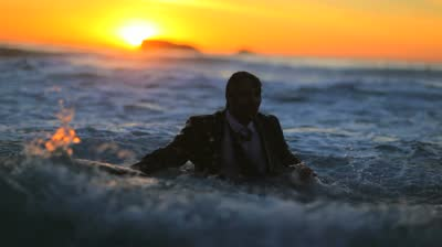 stock-footage-businessman-holding-his-briefcase-in-the-water-during-the-sunset